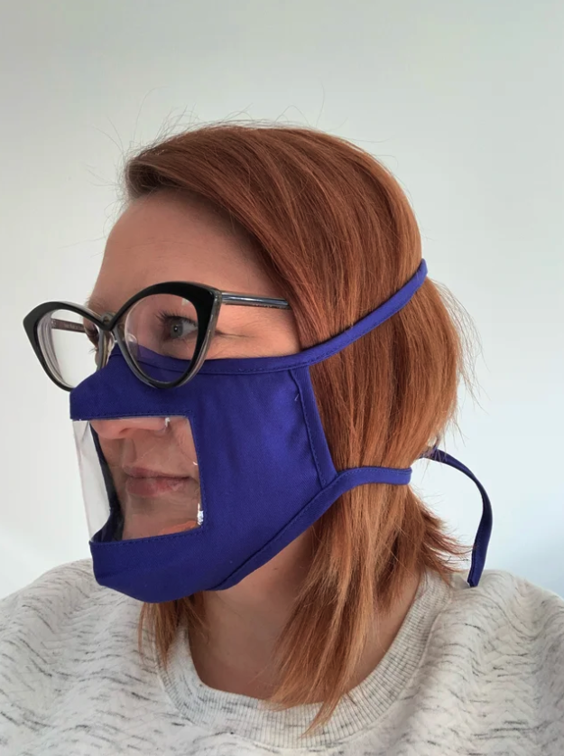 A woman is wearing an accessible protective face mask prototype that has been developed by Soundfair. The mask has a clear window around the mouth and nose area, and is purple. It has elastic loops that go behind the woman's ears. She has red hair, is wearing glasses and a grey jumper.