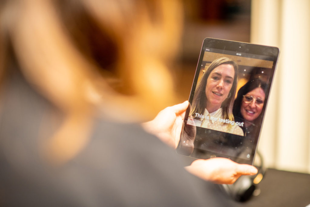 Two women test an accessibility speech to text app at the HearMe art installation.