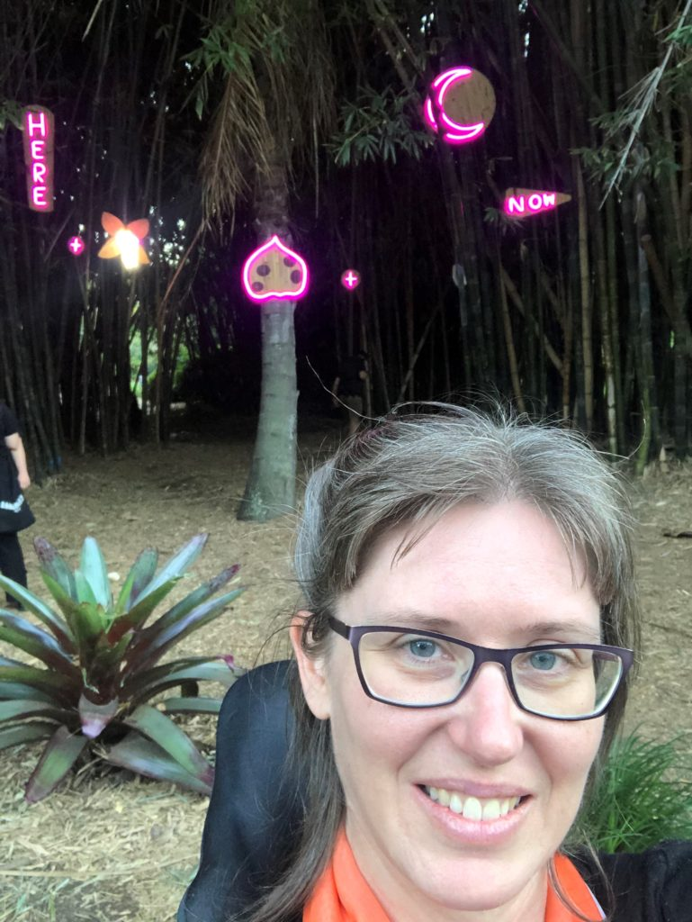 Sarah, smiling and sitting with a backdrop of trees and pink neon signs saying here, now.